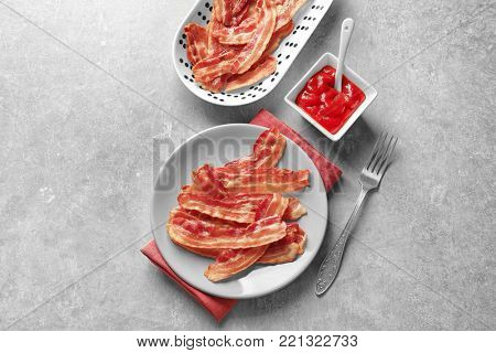 Plates with cooked bacon rashers and sauce on table