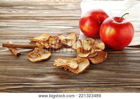 Tasty apple chips and cinnamon sticks on wooden table