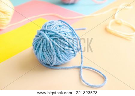 Woolen clew on color background