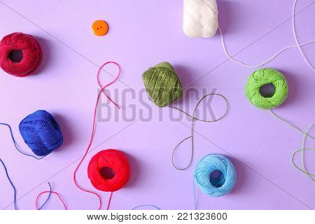 Set of crocheting clews on color background, top view