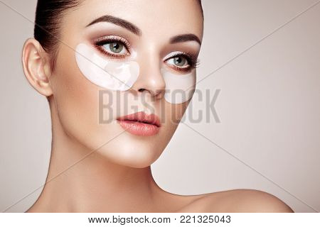 Portrait of Beauty Woman with Eye Patches. Woman Beauty Face with Mask under Eyes. Beautiful Female with natural Makeup and White Cosmetics Collagen Patches on Fresh Facial Skin