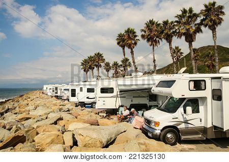 VENTURA COUNTY, CALIFORNIA, USA - OCTOBER 06, 2006. Two probably retired men enjoy a beautiful sunny day surrounded by several RVs on the rocky beaches of Faria Beach National Park.