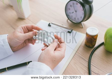 Female doctor holding unlabeled generic tablets and medication, generic drugs concept, prescription medicine and healthcare