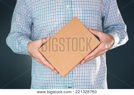 Man holding cardboard box package for mock up design. Courier delivers packed object.