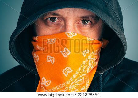 Portrait of masked criminal male person looking at camera. Adult man with hoodie and scarf over face as bandit or gang member, extreme close up