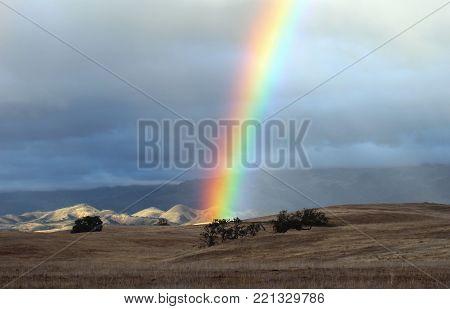 Rainbow touching grass field from dark storm clouds Santa Ynez, California.