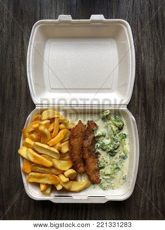 german takeaway food: schnitzel breaded escalope with french fries and broccoli cheese sauce in polystyrene container on rustic wooden table