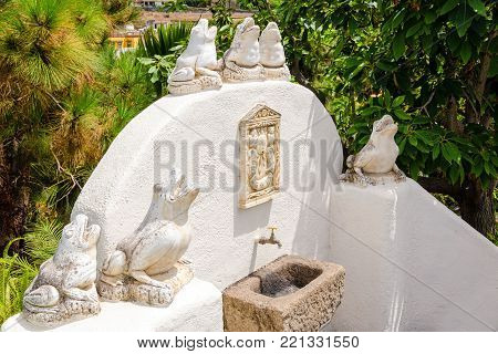 Stone frog statues in a fountain in a landscaped garden. Tenerife, Canary Islands, Spain