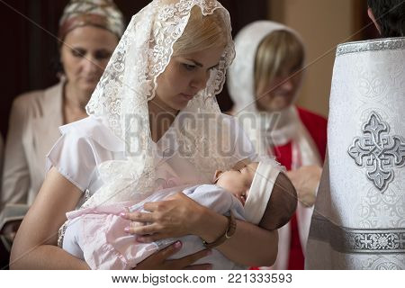 Belarus, the city of Gomel. June 10, 2017. Church at the regional hospital. The baptism of a child.The mother holds the child on her hands during the rite of baptism.Accept religion
