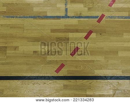 Black, white and red solid or dotted lines in hall playground. Worn out wooden floor of sports hall with colorful marking lines. Schooll gym hall