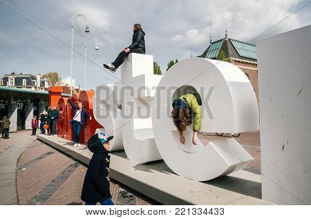 Amsterdam, Netherlands - April 27,2017: Diversity tourists interact with huge letters I Amsterdam - symbol of city.