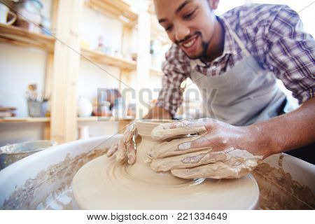 Young master of pottery working by fireclay machine while making jugs