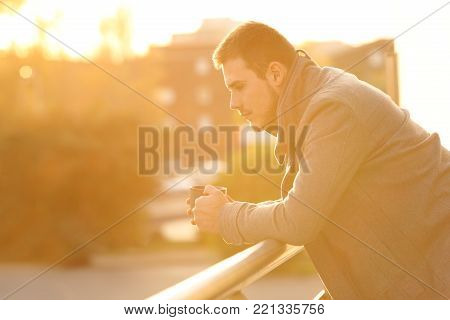 Side view portrait of a sad man looking down in a balcony at sunset in winter