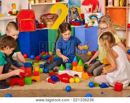 Children building blocks in kindergarten. Group kids playing toy on floor. Top view of interior preschool. Building a tower of cubes. Newcomer in children's team.