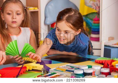 School children with scissors in kids hands cutting paper with teacher in class room. Development and social lerning. Children's project in kindergarten. Newcomer in a children's team.