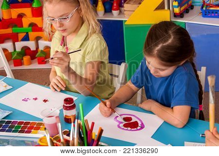 Small students painting in art school class. Child drawing by paints on table. Children study Valentine's Day in kindergarten. Children draw postcards for holiday. Kids in prep school.