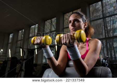 Strong young woman with yellow dumbbells making exercises in gym