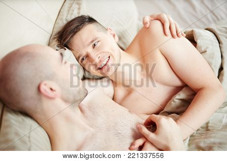Two happy amorous gay men lying in bed, embracing and having talk