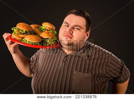 Diet failure of fat man eating fast food. Happy smile overweight person who crazy makes squint for fun eating huge hamburger on fork. Bachelor food. Man suffers from gluttony.