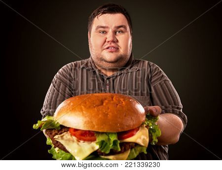 Man eating fast food hamberger. Fat person cooked terrific cheeseburger and admires him, intending to eat it. Junk meal leads to obesity. Consumption of semi-finished products.
