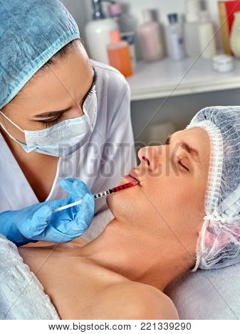 Filler injection for male face. Plastic aesthetic facial surgery in beauty clinic. Man giving anti-aging injections for pull up face contour. Tightening of the skin of the face.