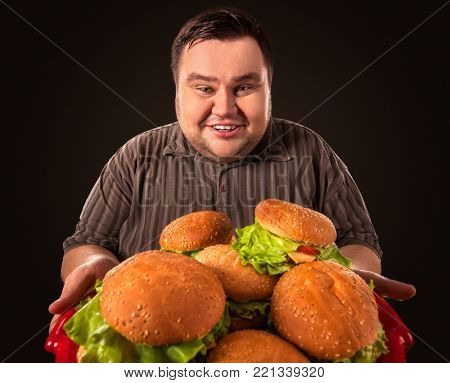 Diet failure of fat man eating fast food. Happy smile overweight person who crazy makes squint for fun eating huge hamburger on fork. Junk meal leads to obesity. Infinite abundance of food.