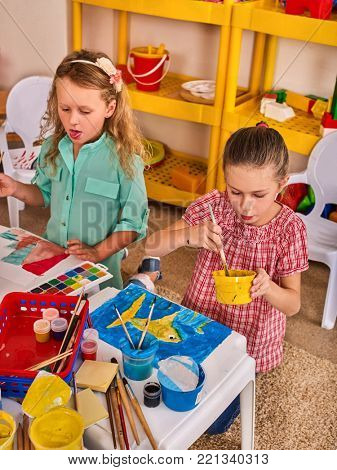 Small students painting in art school class. Child drawing by paints on table. Children learn to mix watercolors in kindergarten. Drawing education develops creative abilities.