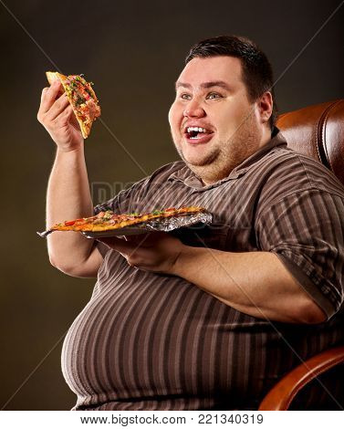 Fat man eating fast food and offers great pizza to customers . Male treats chic junk meal to friends. Breakfast for overweight person. leads to obesity. Consumption of semi-finished products.
