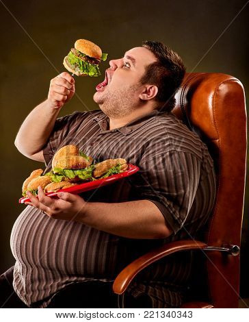 Diet failure of fat man eating fast food hamberger. Happy smile overweight person who spoiled healthy food by eating huge hamburger on fork. Infinite abundance of food. Man rejoices at the end of the