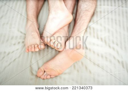 Bare feet and soles of two young gay partners sleeping together poster