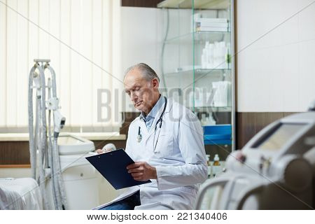 Senior doctor with clipboard making notes in medical card of one of his patients