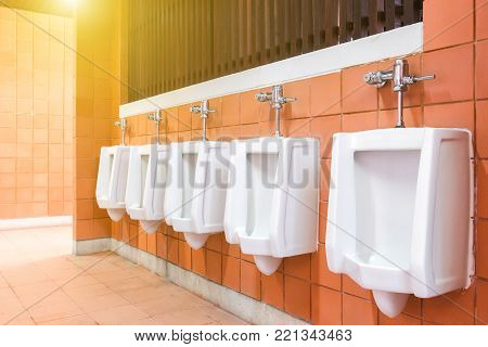 Toilet of man. Tiles wall in the toilet of man with many urinal. Interior of toilet with urinal in the public toilet. Design of white ceramic urinal.