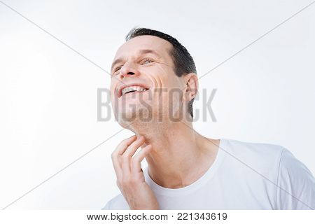 Positive emotions. Nice delighted good looking man touching his neck and smiling while being in a positive mood