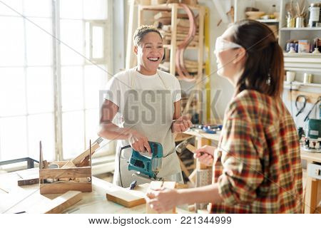 Laughing carpenter with powertool looking at her colleague during talk in workshop