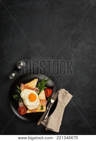 Breakfast or lunch with Fried egg, bread toast, green asparagus, tomatoes and bacon on black plate. Top view. Copy space.