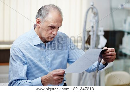 Mature man reading medical paper with information about his x-ray results