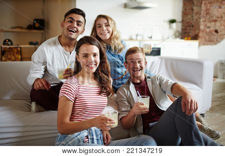 Two happy couples with drinks looking at camera while having fun at home