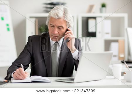 Confident director speaking by smartphone while making notes by workplace