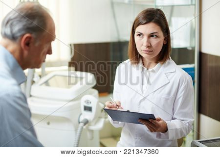 Serious clinician with clipboard listening to aged patient during their conversation
