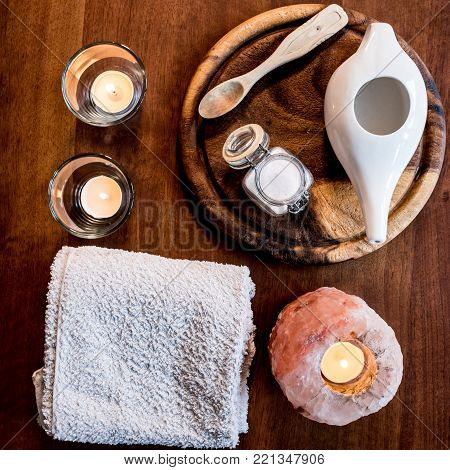 neti pot, ayurvedic system for cleaning nose with water and pink salt from Hymalaia, set with towel, pink hymalaian salt lamp and other candle, spoon and mason jar with salt