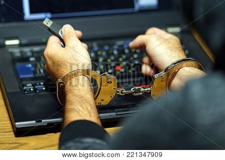 Close-up. Arrested hacker man handcuffed hands. Prisoner or arrested terrorist, close-up of hands in handcuffs, selective focus. Rear view.