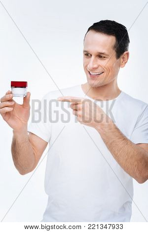 Beauty products. Delighted nice good looking man smiling and pointing at the cream bottle while showing beauty products