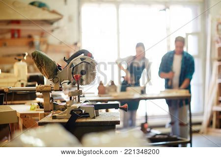 Electric circle saw by workplace of carpenter with two professionals working on background