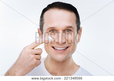 Looking handsome. Joyful nice delighted man looking at you and putting cream of his face while caring about his skin