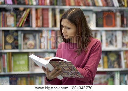 Young girl student woman in a bookstore or library with a serious, thoughtful, concentrated expression in front of her reading an open book. Portrait on the background of bookshelves