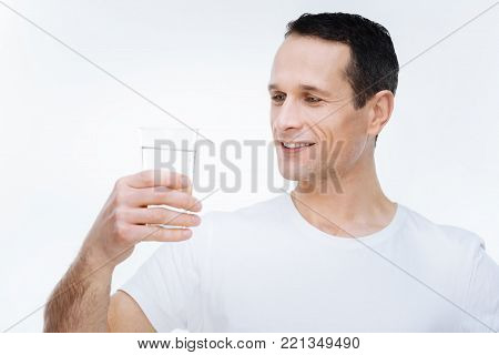Useful drink. Cheerful nice handsome man looking at the glass of water and smiling while enjoying the drink