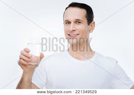 Healthy lifestyle. Delighted nice healthy man smiling and holding a glass of water while leading healthy lifestyle