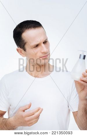 Personal hygiene. Pleasant nice handsome man holding soap and looking at it while standing against white background