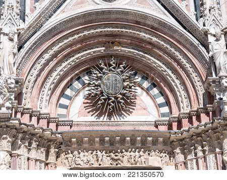 Central portal of the west tacade of the Siena Cathedral shows a bronze sun and many scupltures