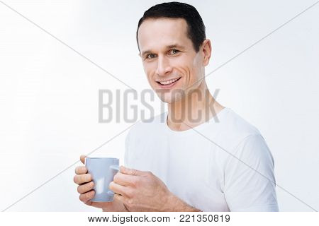 Favourite drink. Positive nice handsome man drinking tea and smiling while looking at you